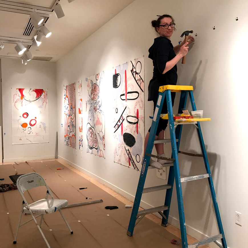 Maria on a ladder installing the Shared Energies exhibition at the Taplin Gallery
