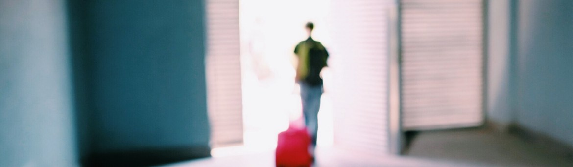 Person with suitcase walking away
