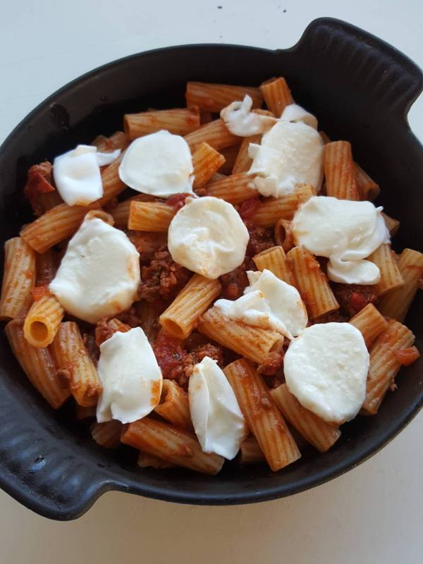 Layering pasta bake with mozzarella