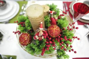 Não é preciso comprar um arranjo pronto. Este foi montado em cima de um prato de bolo, usando velas, enfeites de Natal, ramos artificiais e velas.