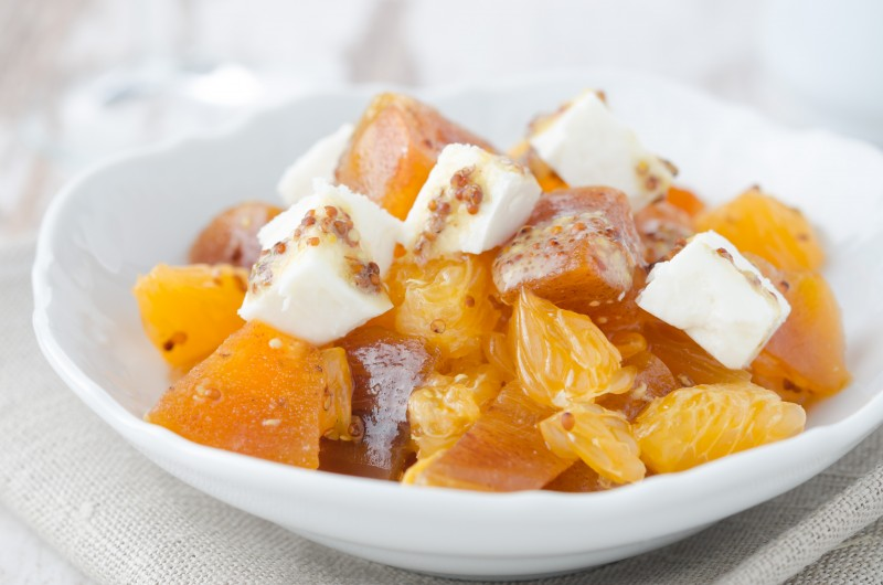 salad with persimmon, mandarin oranges and goat cheese with mustard dressing closeup