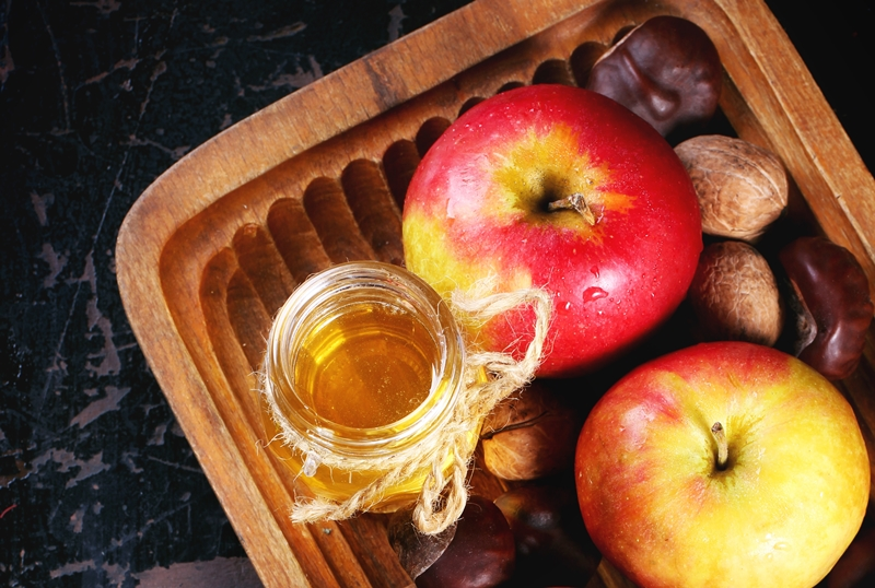 Glass jar of honey with apples, chestnuts and walnuts in wooden plate over black wooden table. Top view