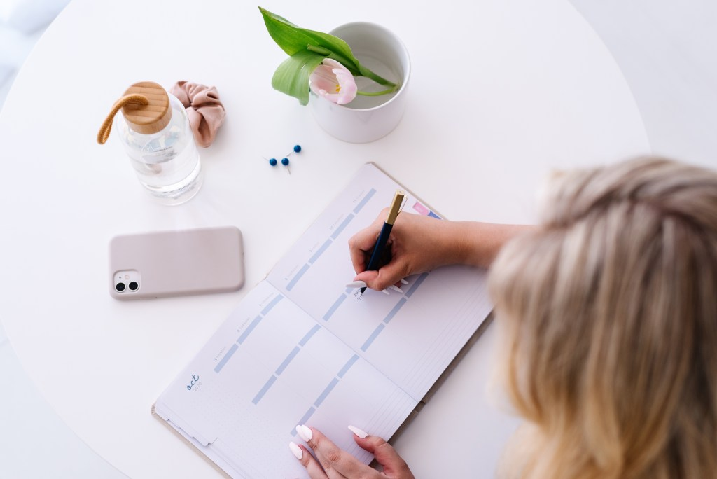 a woman filling her planner