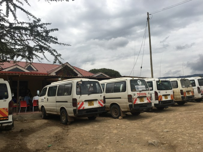 Safari vans at a lunch stop, shuffling passengers to get everyone to the right destionation
