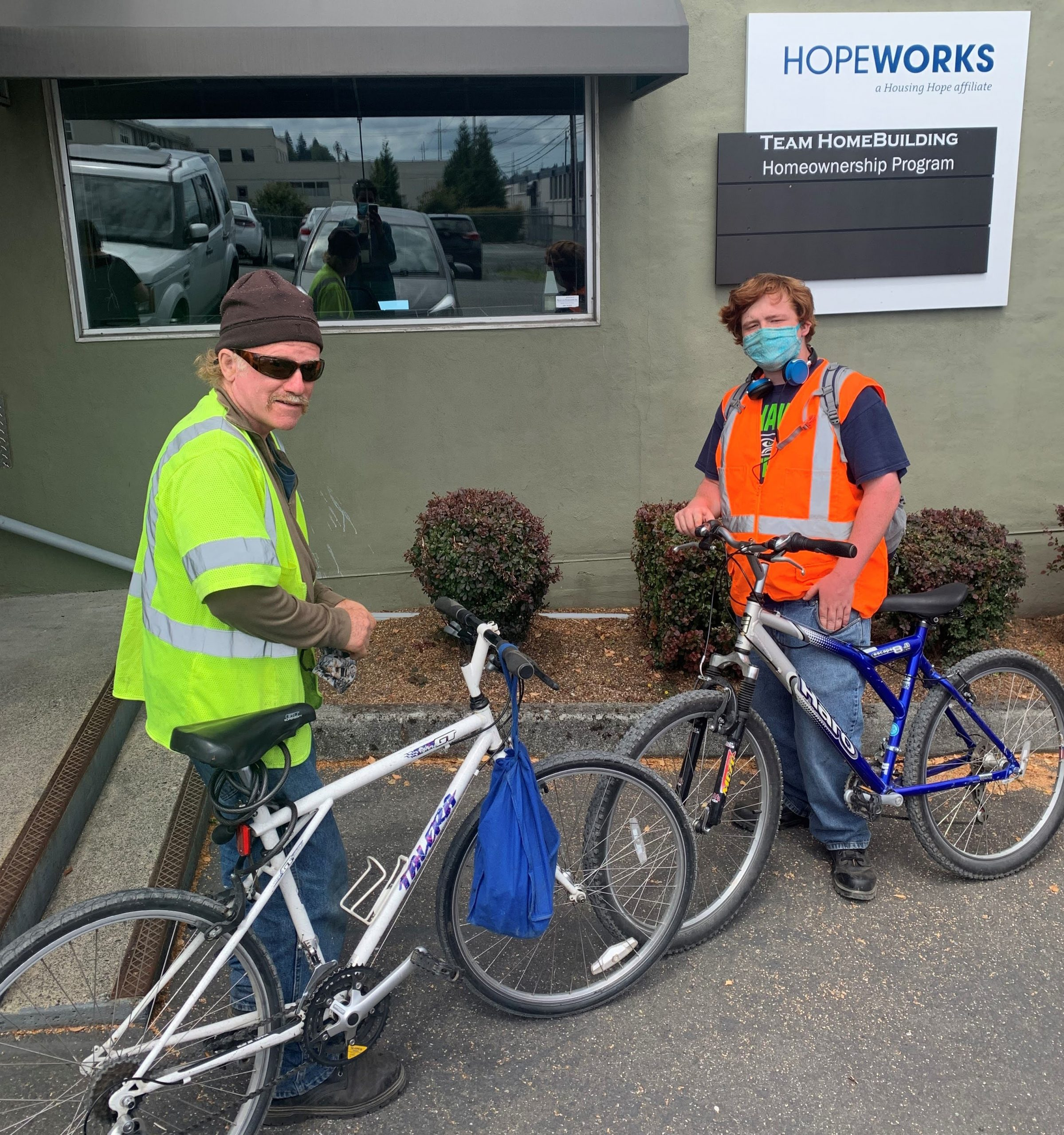 two men with bikes in bright work vests