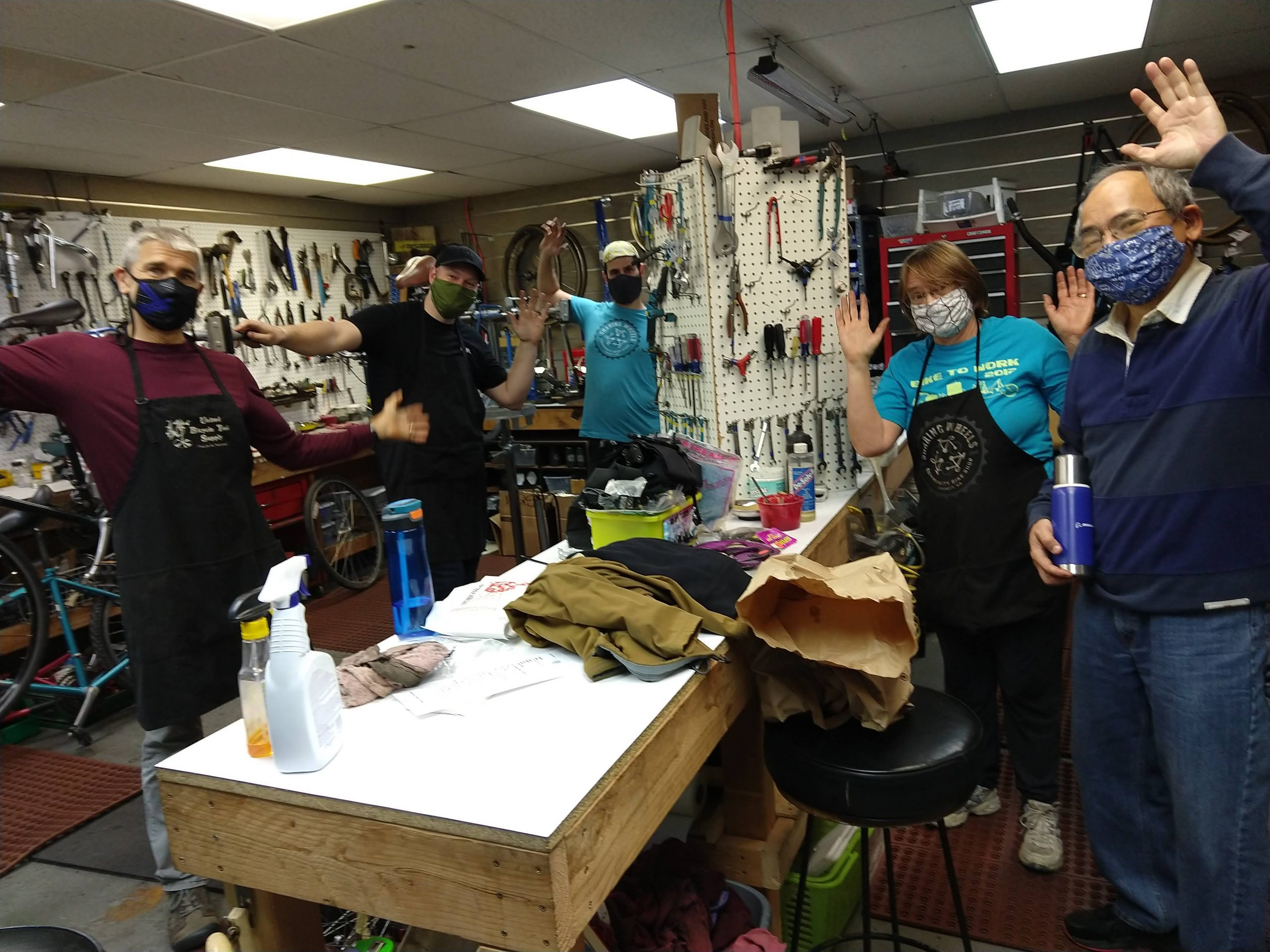 volunteers in masks spread out in the bike shop