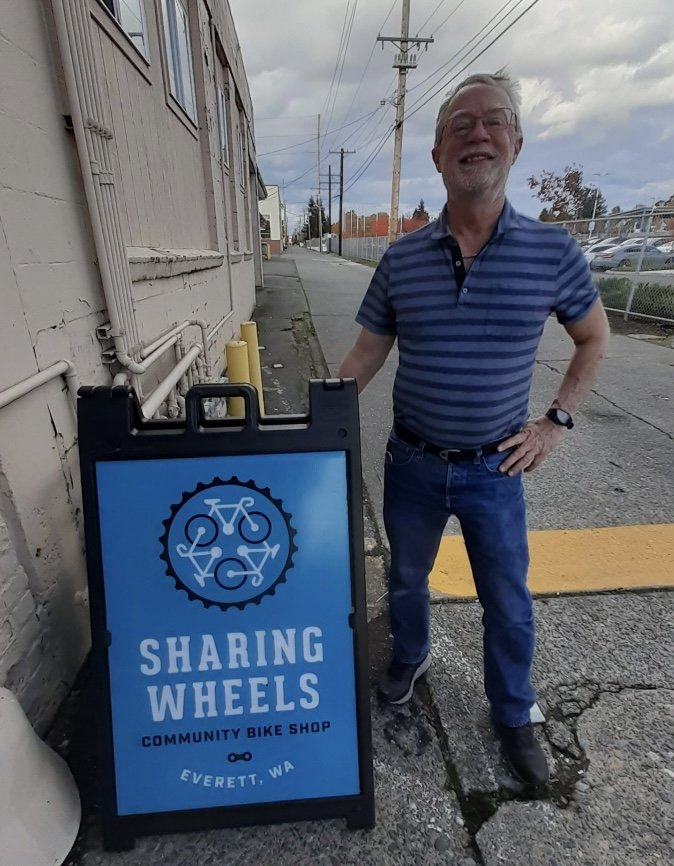 Man standing next to a Sharing Wheels sign