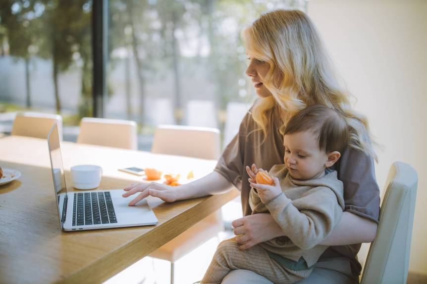 woman carrying her baby and working on a laptop