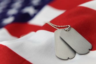 Blank dog tags on American flag with focus on tags - Shallow dof
