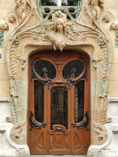 close up of art deco doorway, with angel above and intricate wooden door