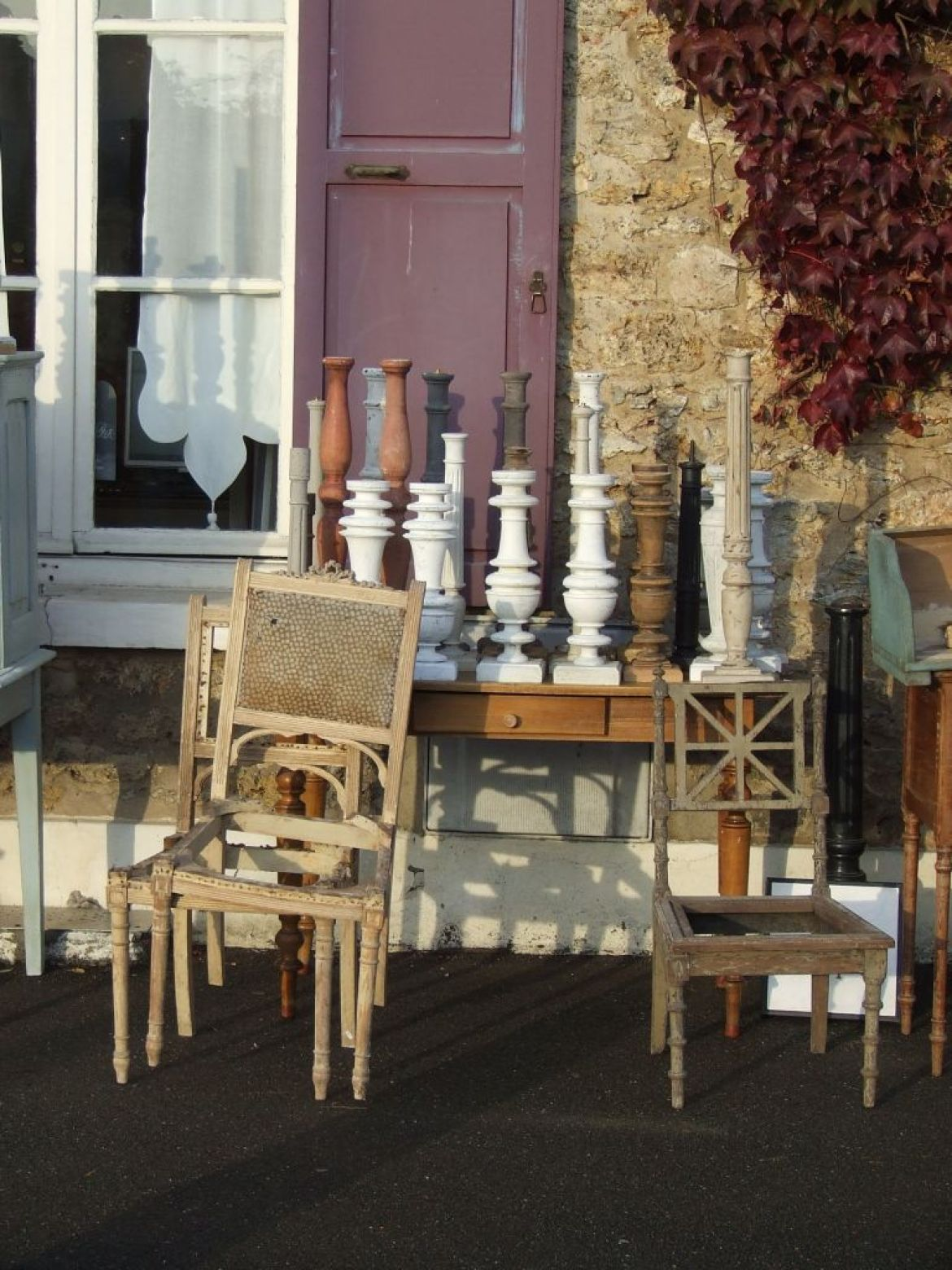 chairs and candlesticks piled up at a brocante fair