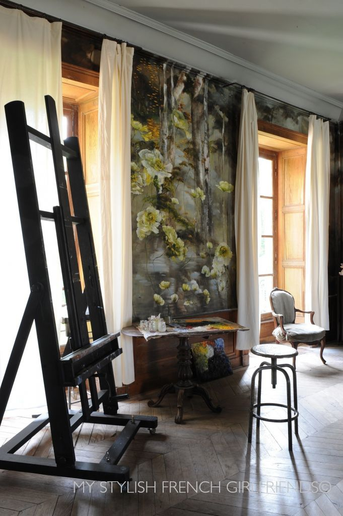 painters easel in room with flowers on wall