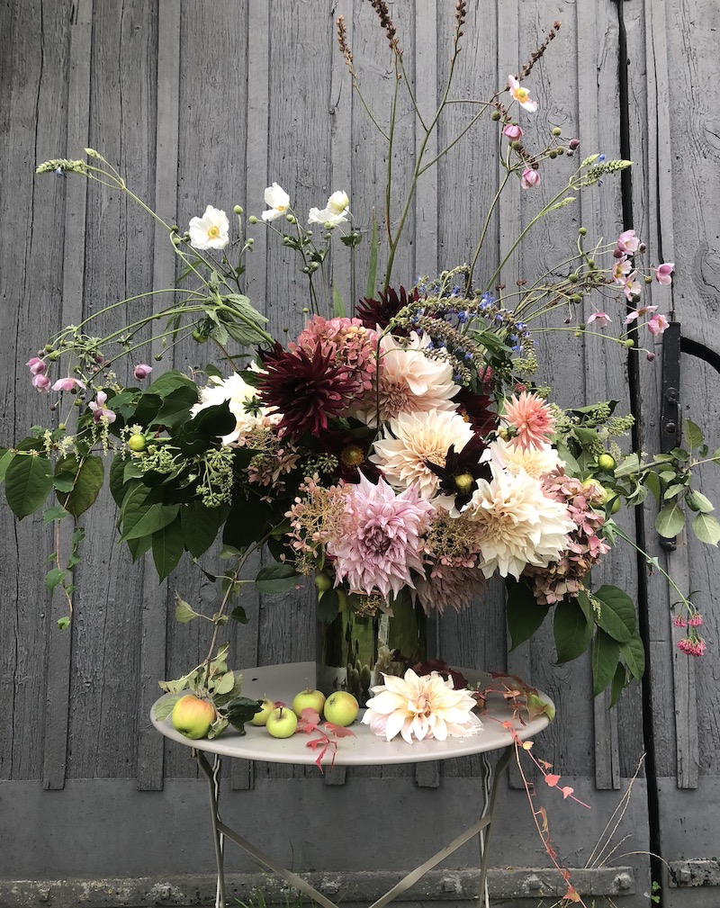 autumn flowers arranged in vase outside barn