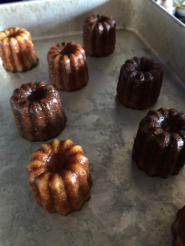 baked caneles on a baking sheet
