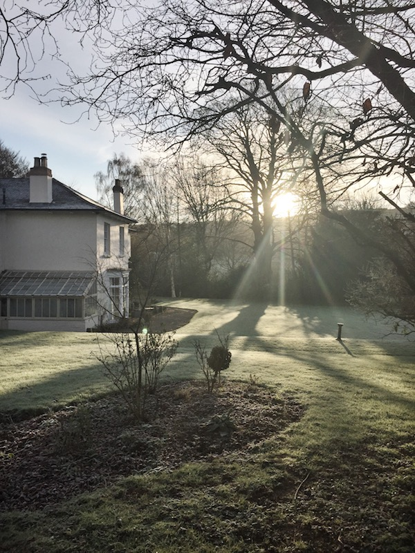 view of white country house at sunset in winter