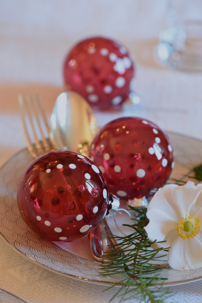 Red glass balls on a white table setting- red christmas decoration ideas- MY FRENCH COUNTRY HOME