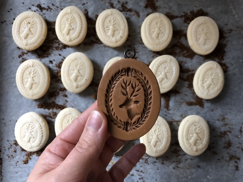 Springerle christmas cookie mold and cookies on a baking tray