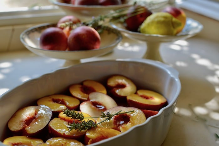 Summer Baked Peaches with Lavender sprigs in a white serving dish