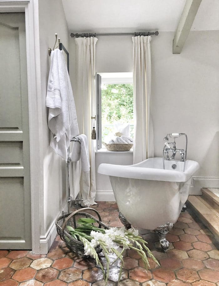 antique bath tub with gorgeous tiled flooring