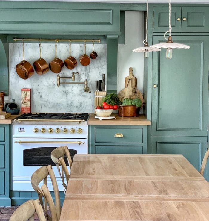 french kitchen with long wooden table, green walls and copper pots and pans