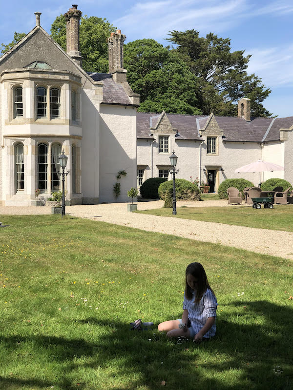 french manor home with child sitting on lawn