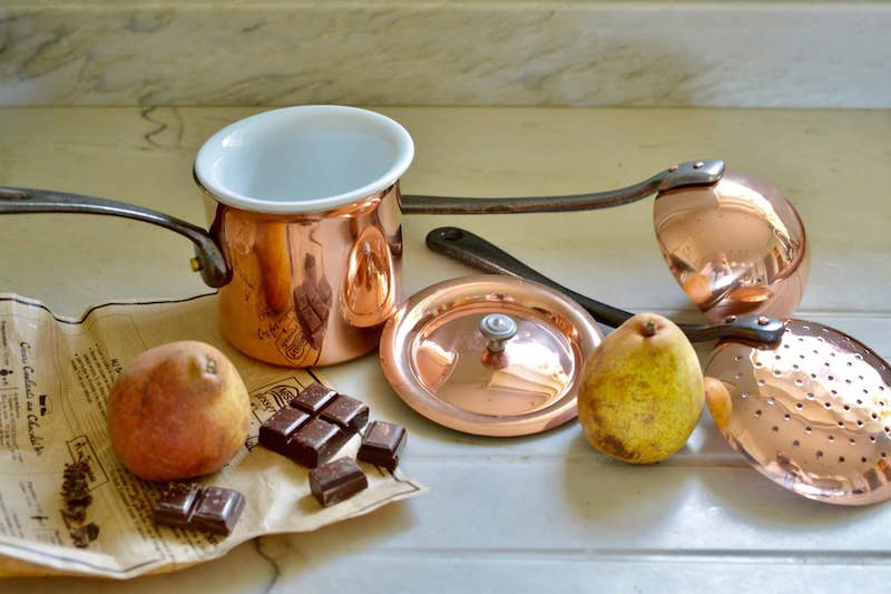 set of copper pans and utensils with pears and chocolate