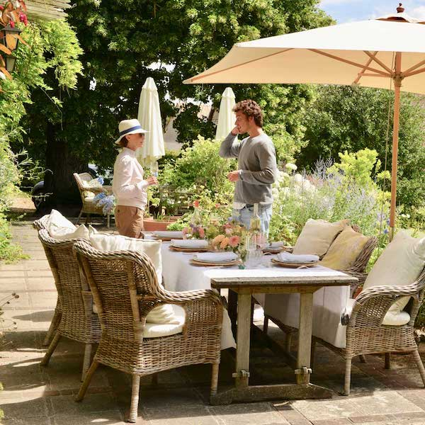 outdoor dining table with umbrella and boy and woman talking