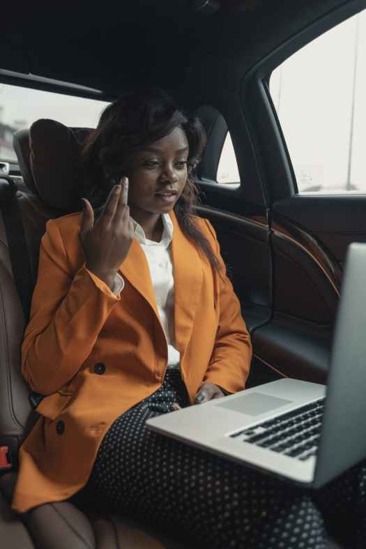 woman in orange blazer sitting inside a car