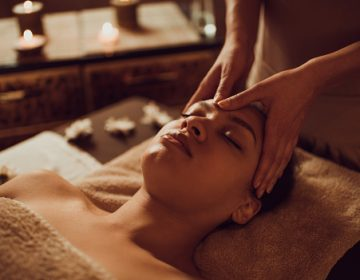 Relaxed black woman having head massage at the spa.