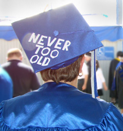 "A graduating student whose cap reads ""never too old""."