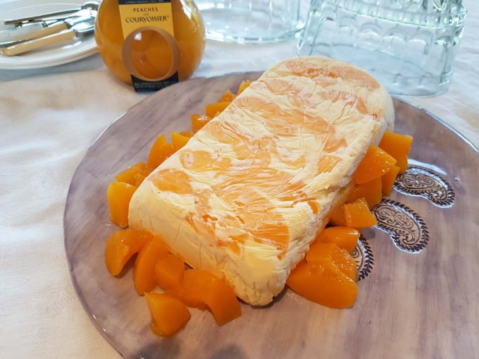 A peach semifreddo with peaches around it on a pretty serving plate