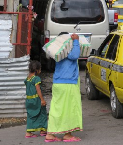 an indian woman with her little daughter carrying the rice for the next months - everyone has a different coulor of the traditional dress for the women