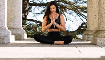 woman in black tank top and black pants sitting on concrete floor to meditate