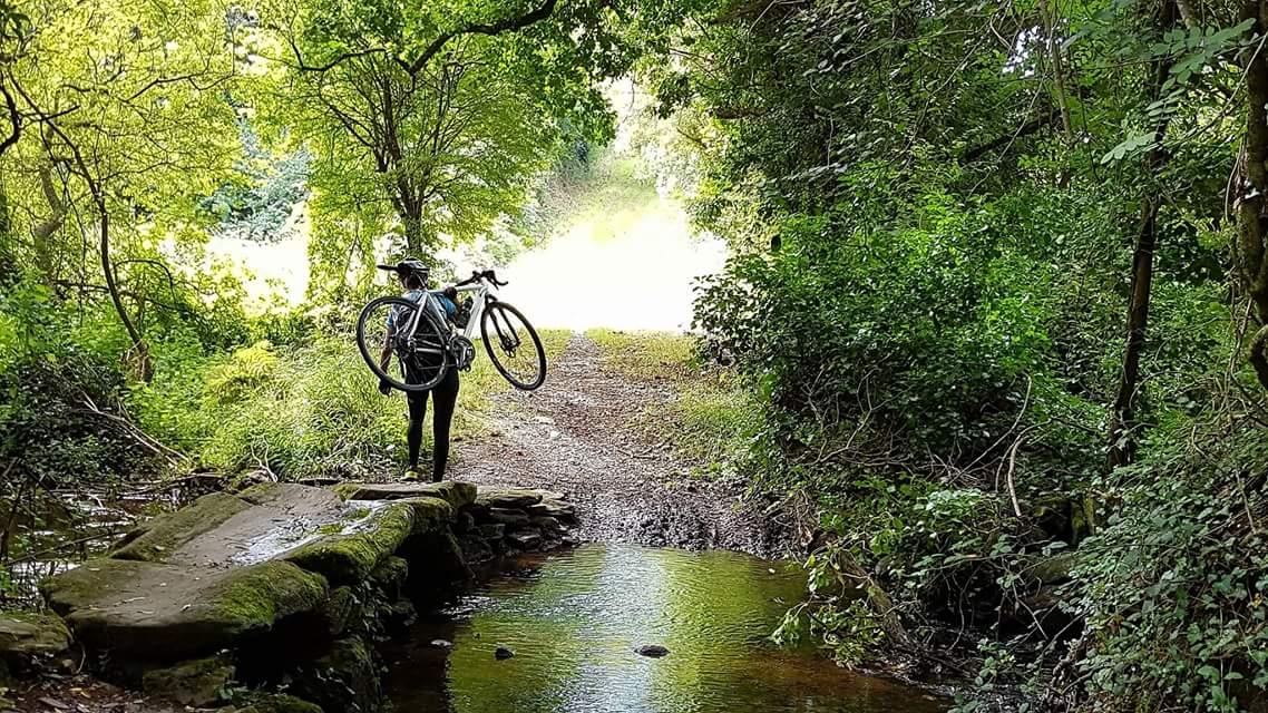 Andrea Freiermuth trägt ihr Fahrrad über einen Steg im Wald