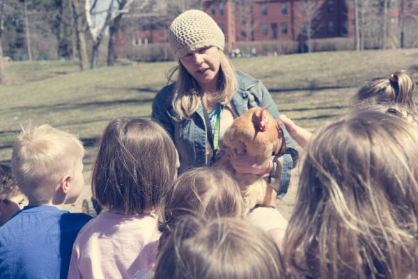 SHED Children's Campus Executive Director shows a hen to children