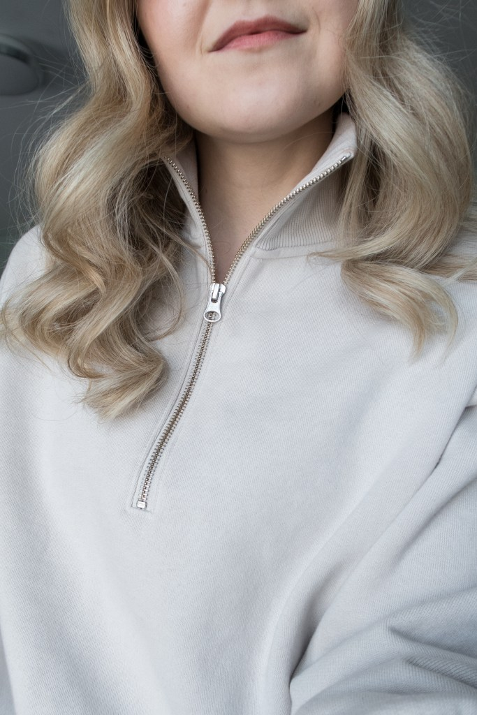 A blonde woman posing in an Everlane half-zip stone-coloured sweater