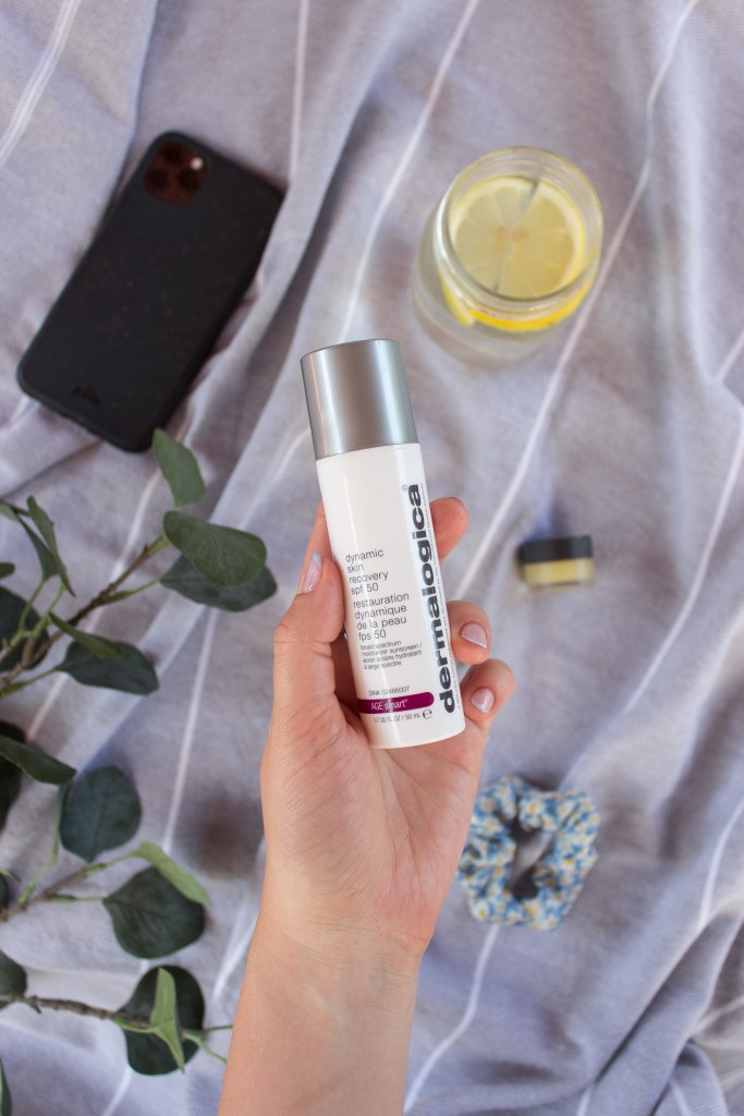 "A hand holding the ""Dynamic Skin Recovery SPF50"" by Dermalogica with a phone, lemon water, scrunchie, lip balm and leafed branches in the background"