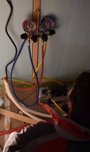 """Brad watching the gauges as he """"pulls a vacuum"""" on our mini-split lines to test for leaks."""
