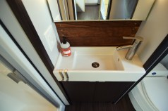 Bathroom sink alcove with reclaimed walnut accents