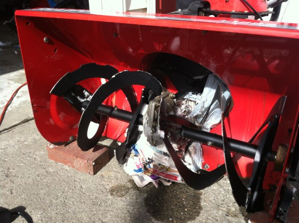 newspaper-jammed snow blower auger