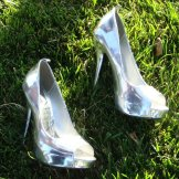 Photo of a pair of shiny, metallic silver high heels sparkling off the matte of green grass
