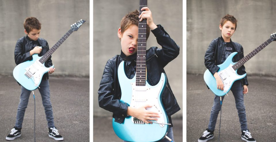 Portraits of young boy with electric guitar