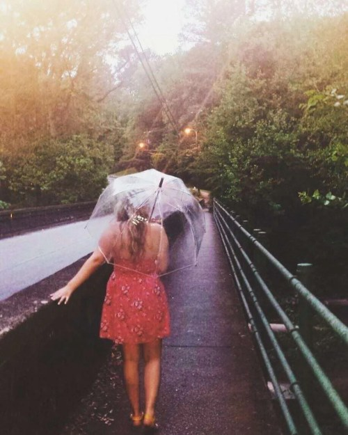 woman walking on a bridge in the rain with a clear umbrella