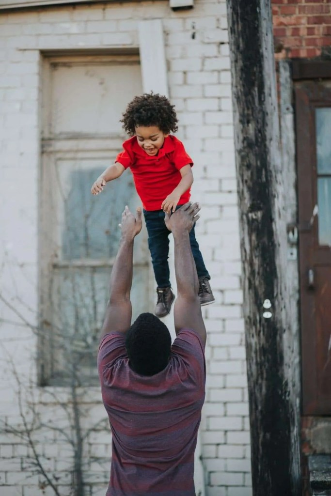 Father playing with son, throwing him in the air