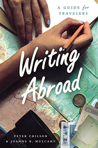 Cover of Writing Abroad, showing a pair of hands with a pencil writing in a notebook on top of a map