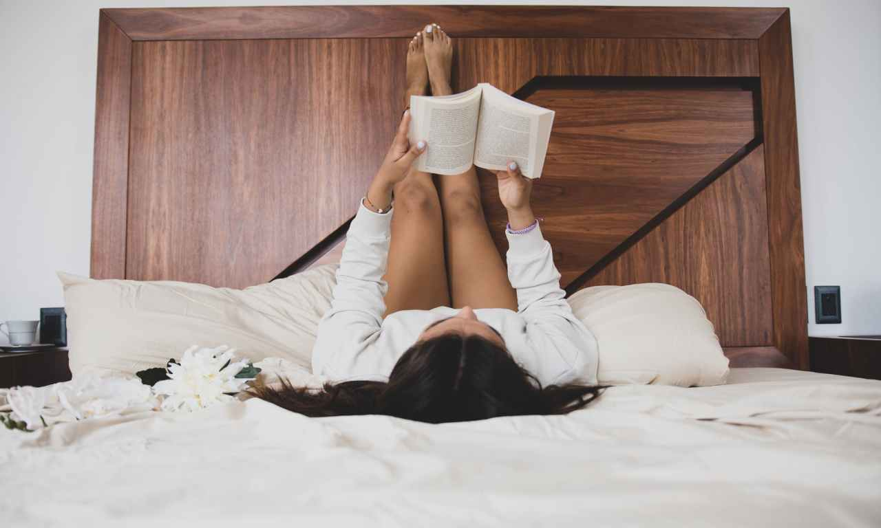 woman in white dress shirt and black pants lying on bed reading book