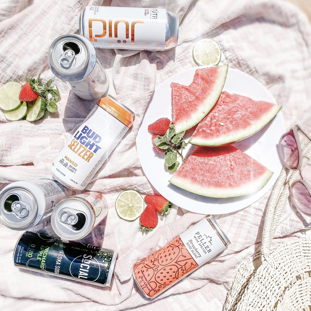 Low-Calories Summer Alcoholic Coolers laid on a picnic blanket with fresh fruit. Low-Calorie 2021 Summer Alcoholic Drink Review: The best low-sugar alcoholic coolers available in stores now at the LCBO.