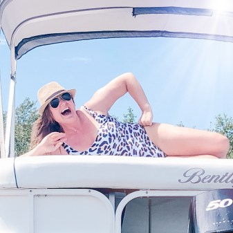 girl on a boat feeling confident in a leopard print bathing suit