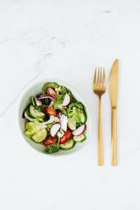 Fresh Garden Salad on a granite kitchen counter with gold cutlery