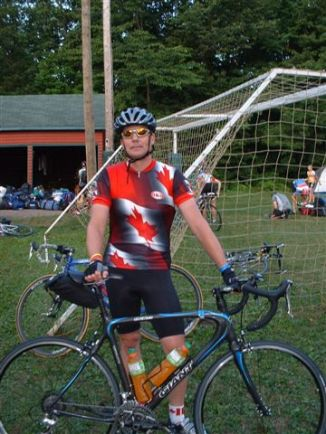 This i a photo of a middle-aged Caucasian man wearing cycling gear and standing with a bike on a soccer field
